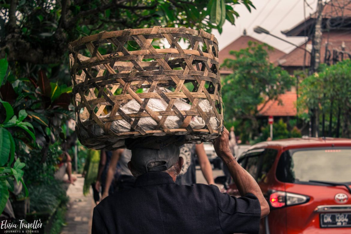 A man carrying miscellaneous items on his head on Monkey Forest road